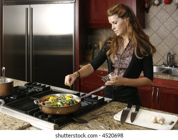 Beautiful young woman adding herbs to vegtable dish in frying pan on gas stove.
