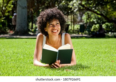 Beautiful young woman of African descent reading a book in a park