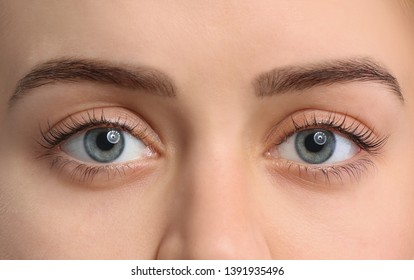 Beautiful young woman after eyelashes lamination on white background, closeup