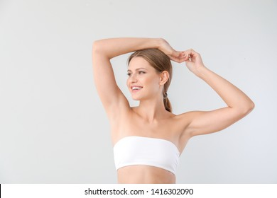 Beautiful young woman after laser hair removal procedure on light background