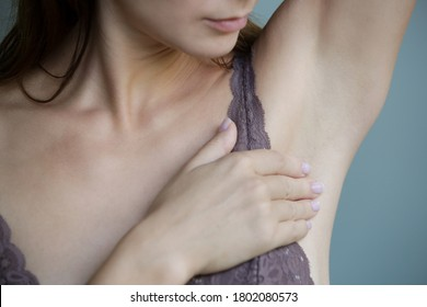Beautiful young woman after shower at home examining armpit. Armpit lumps or swollen armpit glands.