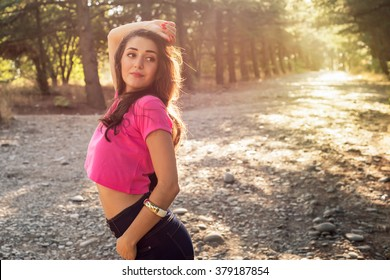 Beautiful young woman in against the sun background