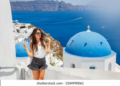 Beautiful young woman against white architecture of Santorini