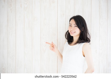 beautiful young woman against white wooden wall