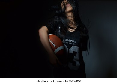 beautiful young woman, american football concept, studio shot