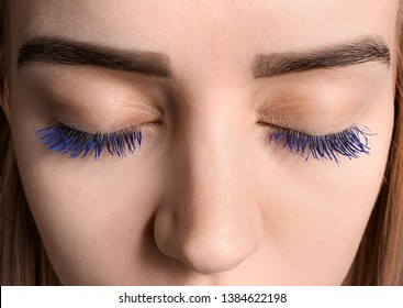 Beautiful young woman with applied color mascara, closeup