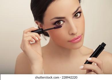 beautiful young woman applied mascara, studio beauty portrait