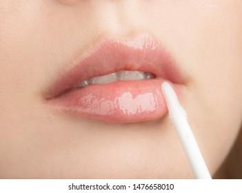 Beautiful Young Woman Apply Moisturizing Lip Gloss