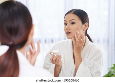 Beautiful young woman applying anti-aging cream on her face