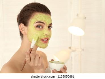 Beautiful young woman applying avocado facial mask in bathroom
