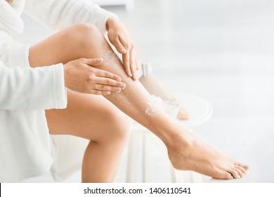 Beautiful young woman applying body scrub at home