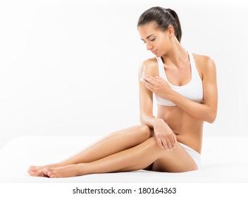 Beautiful young woman applying body lotion.