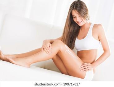 Beautiful young woman applying body lotion
