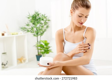 Beautiful young woman applying body lotion.