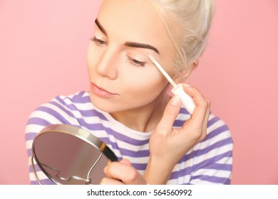Beautiful young woman applying concealer on eyelid