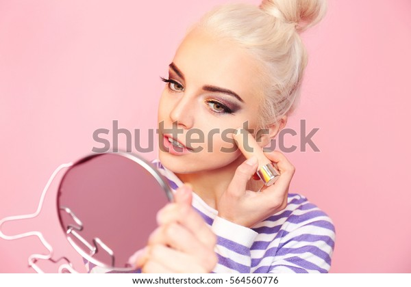 Beautiful young woman applying concealer stick