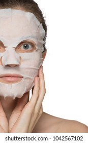 Beautiful young woman is applying a cosmetic tissue mask on a face on a white background