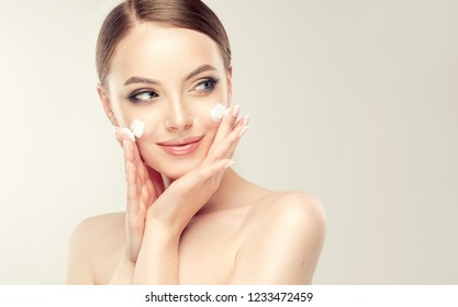 Beautiful young woman applying cosmetic cream treatment on her face isolated on background . Girl with clean fresh skin .Spa and cosmetology .