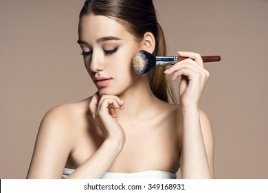 Beautiful young woman applying cosmetic powder on her face with tassel, skin care concept / photo composition of brunette girl on beige background