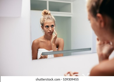 Beautiful young woman applying cosmetic cream on face standing in the bathroom. Reflection in female doing skin treatment.