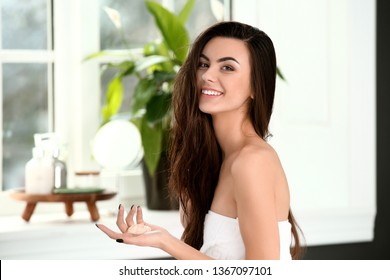Beautiful young woman applying cosmetics onto her healthy long hair at home