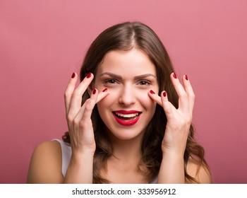 Beautiful young woman applying an eye cream
