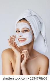 Beautiful young woman applying facial mask on her face. Skin care and treatment, spa, natural beauty and cosmetology concept, over white background