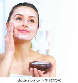 Beautiful Young Woman applying facial homemade Mask at home. Spa and skin care concept