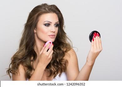 Beautiful young woman applying foundation using beauty sponge. Closeup, no retouch, studio lighting.
