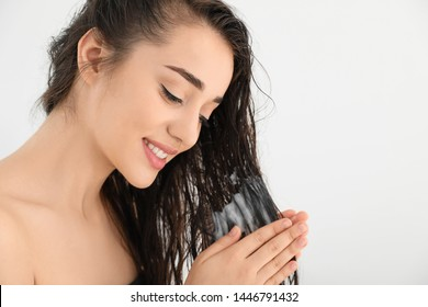 Beautiful young woman applying hair conditioner against white background. Space for text