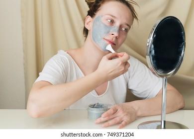 Beautiful young woman applying a hydrating bubble mask