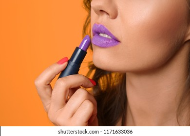 Beautiful young woman applying lilac lipstick on color background, closeup
