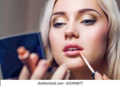 Beautiful young woman applying lips makeup with cosmetic brush