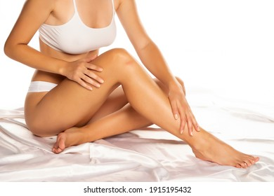 Beautiful young woman applying lotion on her legs, isolated on white.