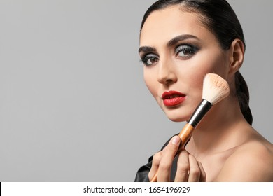 Beautiful young woman applying makeup against grey background