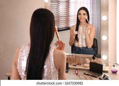 Beautiful young woman applying makeup near mirror in dressing room