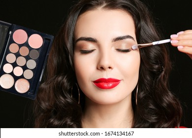 Beautiful young woman applying makeup on dark background