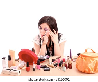 Beautiful young woman applying makeup on eye