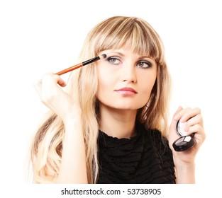 beautiful young woman applying makeup with brush
