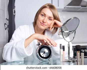 beautiful young woman applying makeup at home