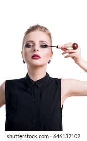 Beautiful young woman applying mascara with brush, studio beauty portrait. Applying cosmetic, eyes makeup. Dark evening make-up and jewelry in beauty concept. Fashion photo