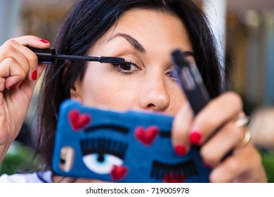 Beautiful young woman applying mascara on her eyes using her smart phone as mirror