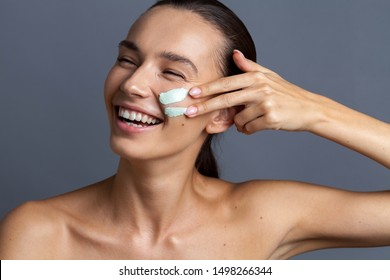 Beautiful young woman applying mask on face, closeup
