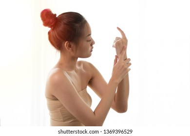 beautiful young woman applying nourishing  body lotion to her smooth skin to soften and hydrates the skin body