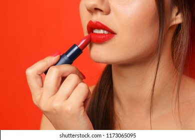 Beautiful young woman applying red lipstick on color background, closeup