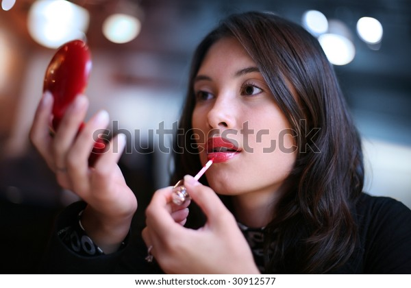 Beautiful young woman applying red lip gloss, looking in small mirror. Shallow DOF.