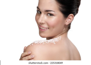Beautiful young woman applying scrub treatment on the skin  on white
