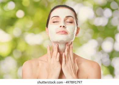 Beautiful young woman applying scrub mask on face on blurred nature background