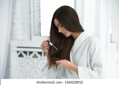 Beautiful young woman applying serum onto her healthy long hair at home