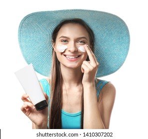 Beautiful young woman applying sun protection cream against white background